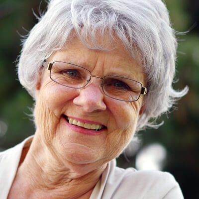 Woman with fixed dentures smiling.